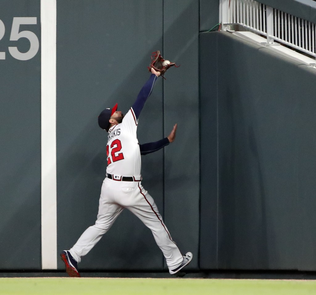Atlanta Braves right fielder Nick Markakis (22) makes a catches a fly ball at the wall from Philadelphia Phillies catcher Jorge Alfaro in the seventh