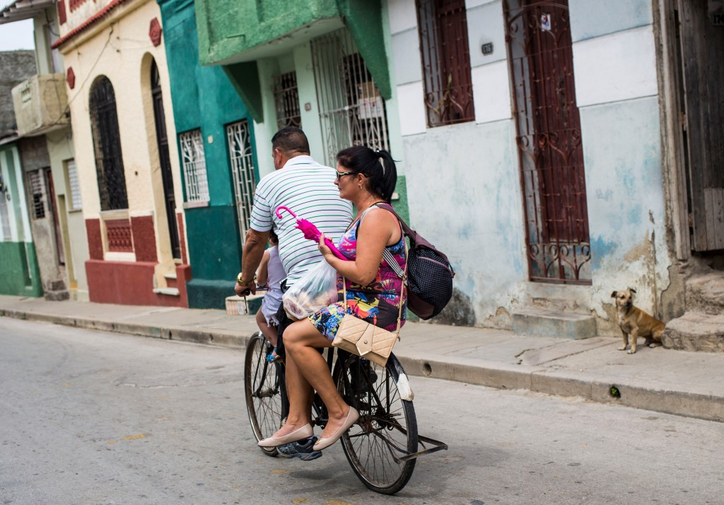 In this April 1, 2018 photo, three people share a bicycle along San Miguel Street where Miguel Mario Diaz-Canel Bermudez lived in Santa Clara, Cuba. D