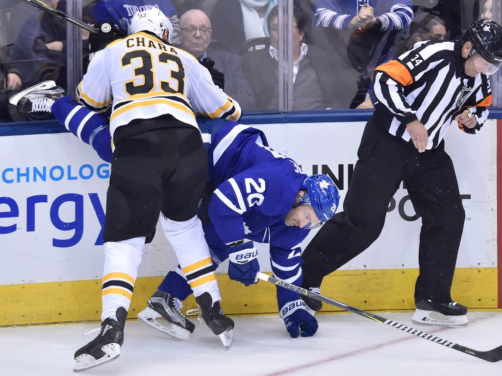 Toronto Maple Leafs centre Dominic Moore (20) takes a hits from Boston Bruins defenseman Zdeno Chara (33) during third period NHL round one playoff ho
