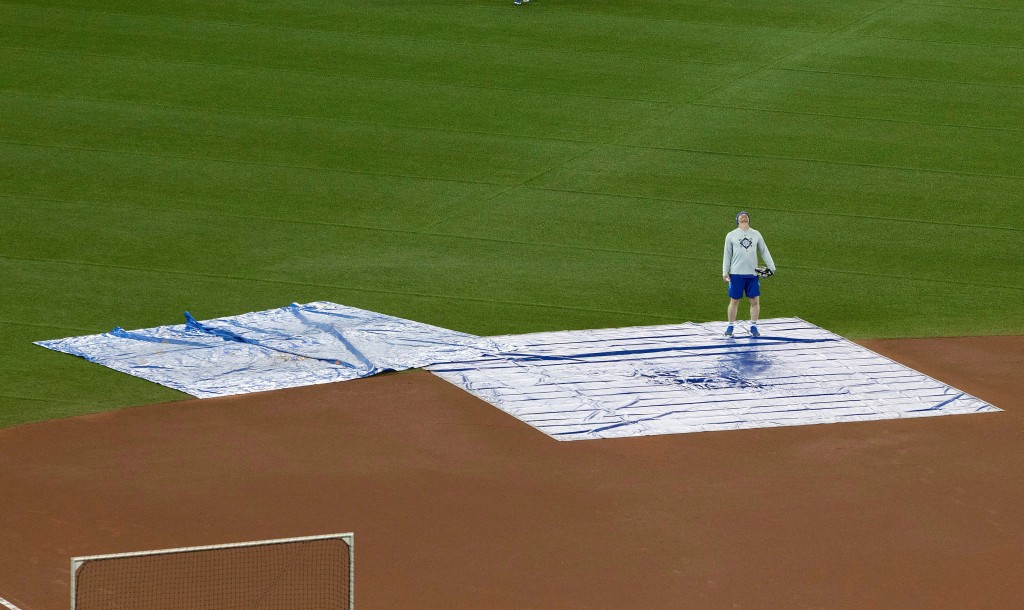 Toronto Blue Jays coach Tim Leiper looks up from tarps protecting the field at Rogers Centre from water coming through the roof in Toronto on Monday A