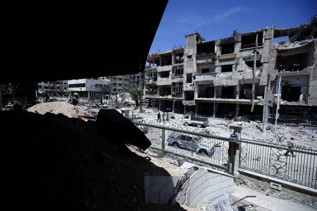 Syrians walk through the destruction in the town of Douma, the site of a suspected chemical weapons attack, near Damascus, Syria, Monday, April 16, 20
