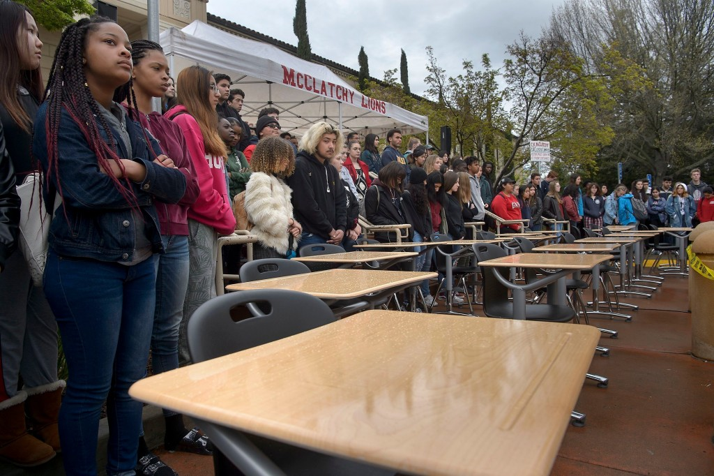 FILE- In this March 14, 2018, file photo, students gather around 17 empty desks representing the shooting victims from Marjory Stoneman Douglas High S