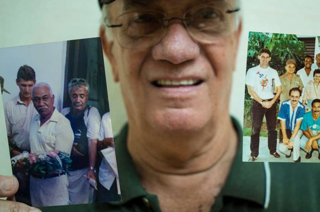 In this April 2, 2018 photo, radio journalist Normando Hernandez Castro, 70, shows pictures with himself with Miguel Mario Diaz-Canel Bermudez in Sant
