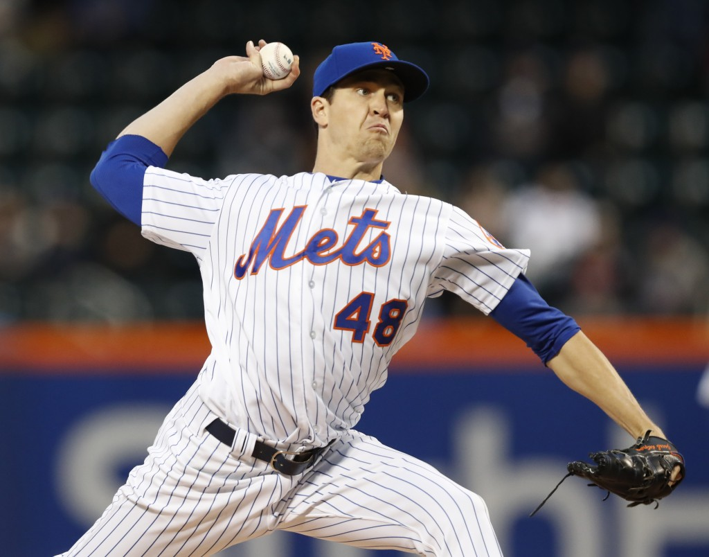 New York Mets starting pitcher Jacob deGrom winds up as he delivers a pitch during the first inning of a baseball game against the Washington National