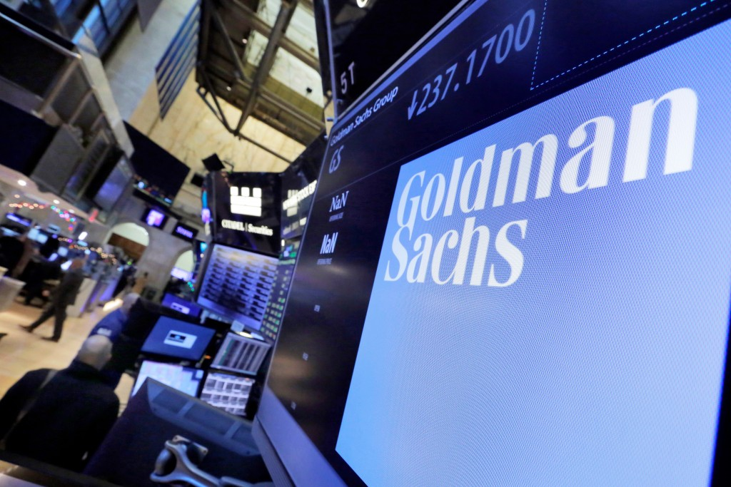 FILE - In this Dec. 13, 2016, file photo, the logo for Goldman Sachs appears above a trading post on the floor of the New York Stock Exchange. The Gol