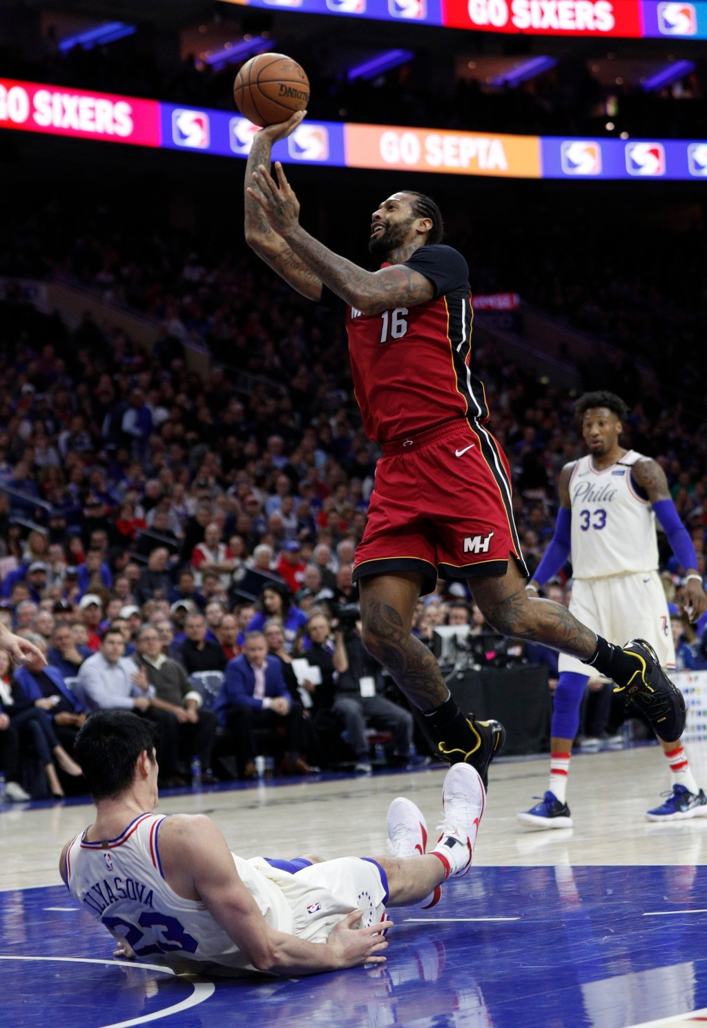 Miami Heat's James Johnson, right, shoots and draws the foul call on Philadelphia 76ers' Ersan Ilyasova, left, of Turkey, during the first half in Gam