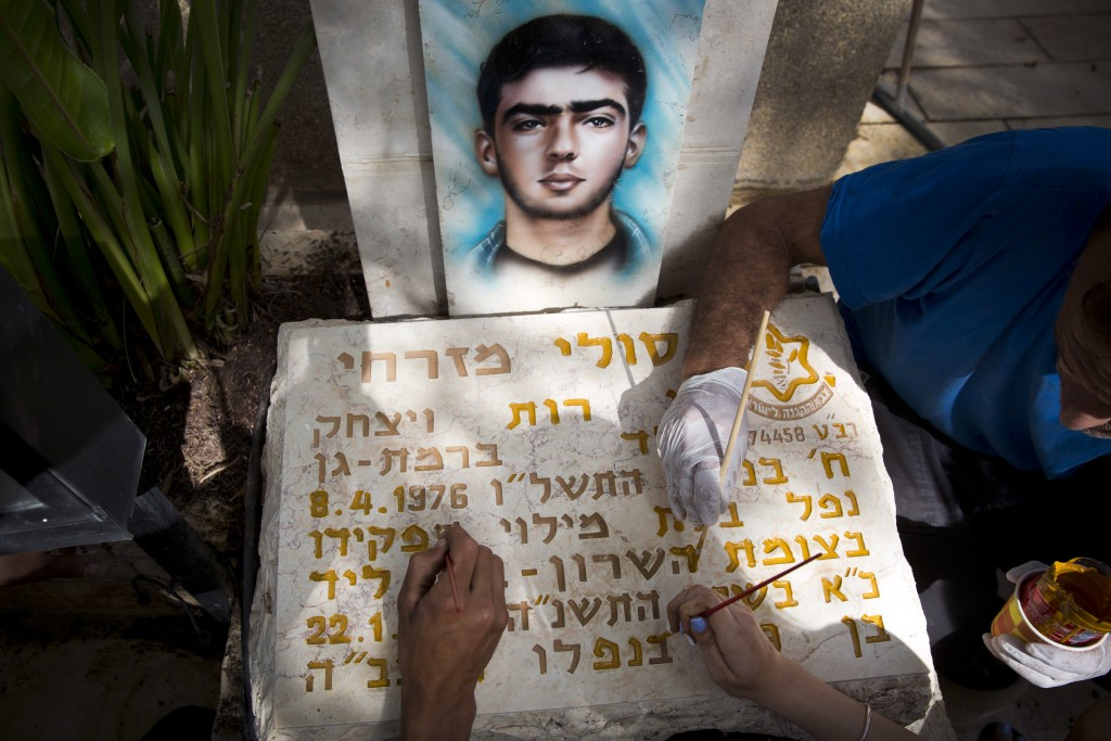 Family members of Israeli soldier Soli Mizrahi repaint his gravestone at Kiryat Shaul military cemetery on the eve of memorial Day in Tel Aviv, Israel