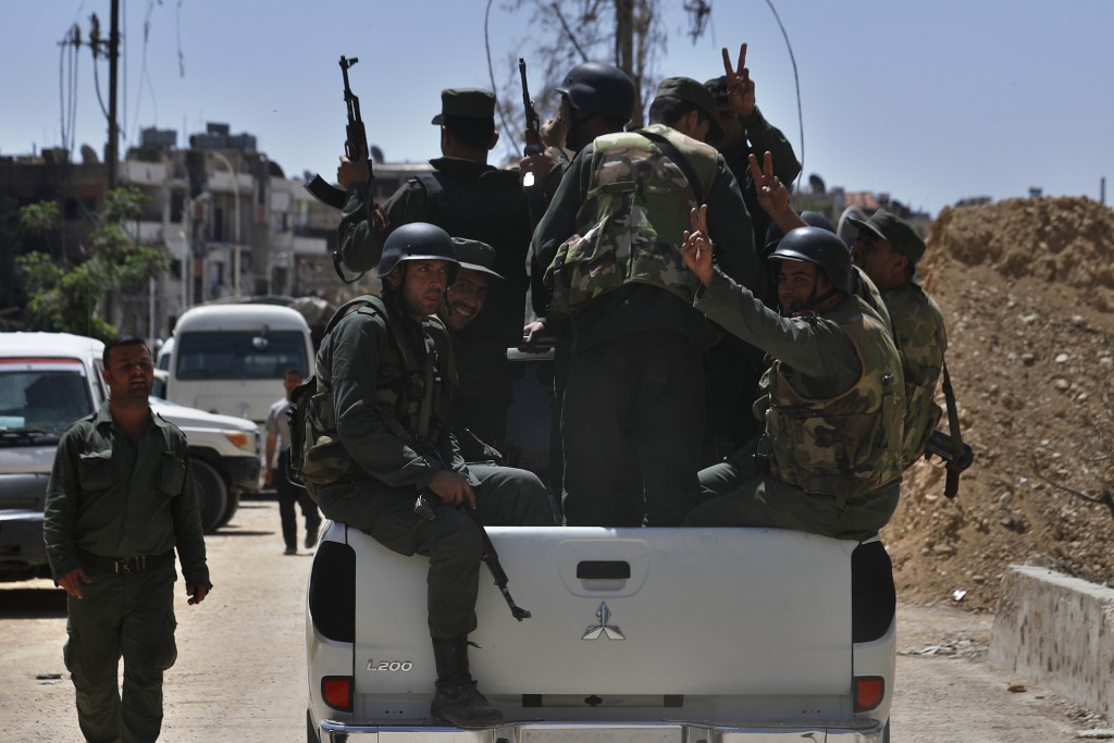 Syrian police units wave and give the victory sign as they patrol in the town of Douma, the site of a suspected chemical weapons attack, near Damascus