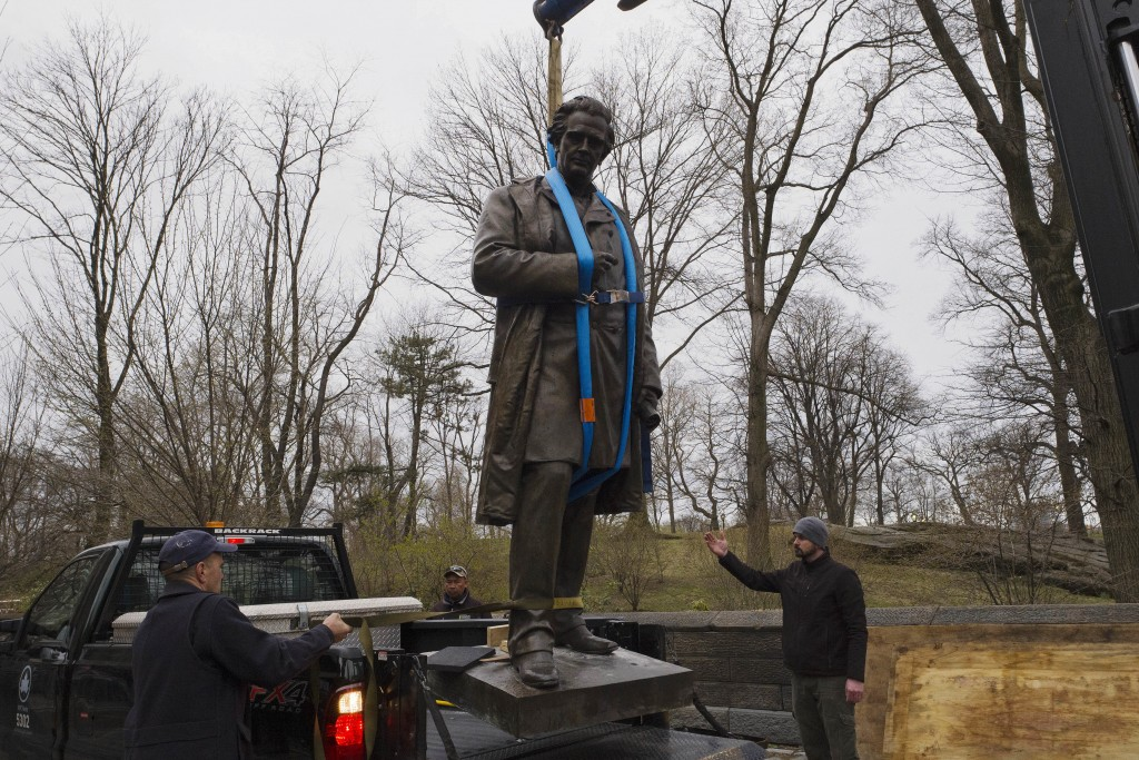 The statue of Dr. J. Marion Sims, is removed by crane, Tuesday, April 17, 2018, in New York's Central Park.  Sims was known as the father of modern gy