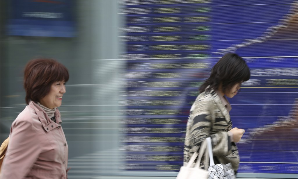 People walk by an electronic stock board of a securities firm in Tokyo, Tuesday, April 17, 2018. Asian shares were mostly higher but little changed Tu