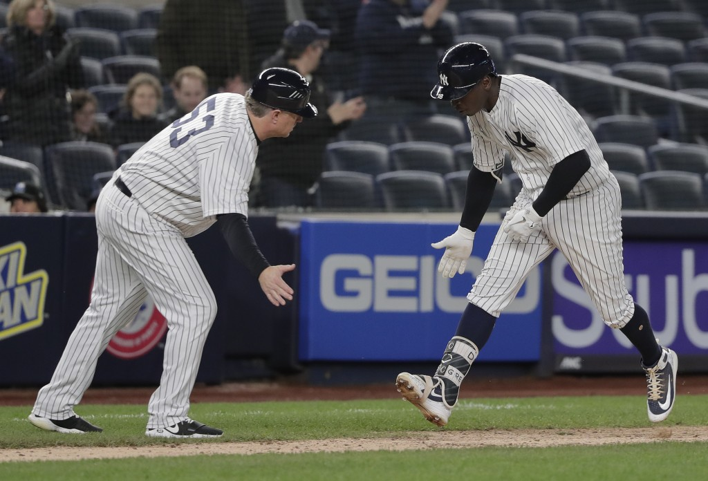 New York Yankees' Didi Gregorius is congratulated by third base coach Phil Nevin (53) after hitting a solo home run against the Miami Marlins during t
