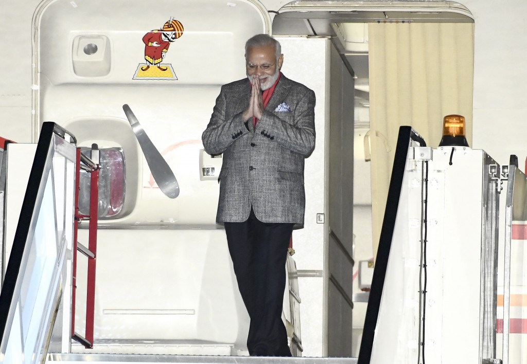 India's Prime Minister Narendra Modi emerges from his plane as he is welcomed on arrival at Arlanda Airport in Stockholm, Sweden, Monday April 16, 201