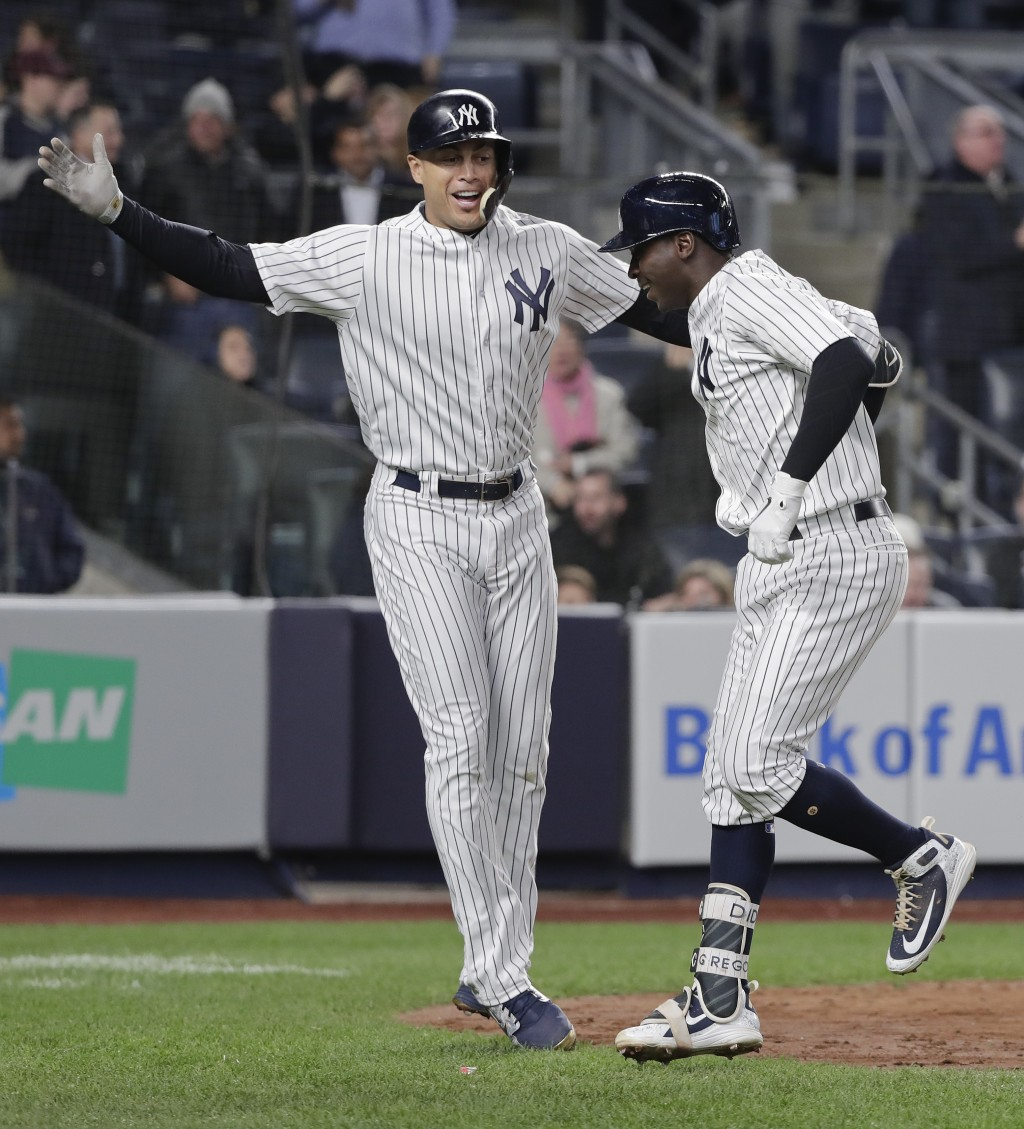 New York Yankees' Giancarlo Stanton, left, celebrates with Didi Gregorius after Gregorius hit a two-run home run against the Miami Marlins during the