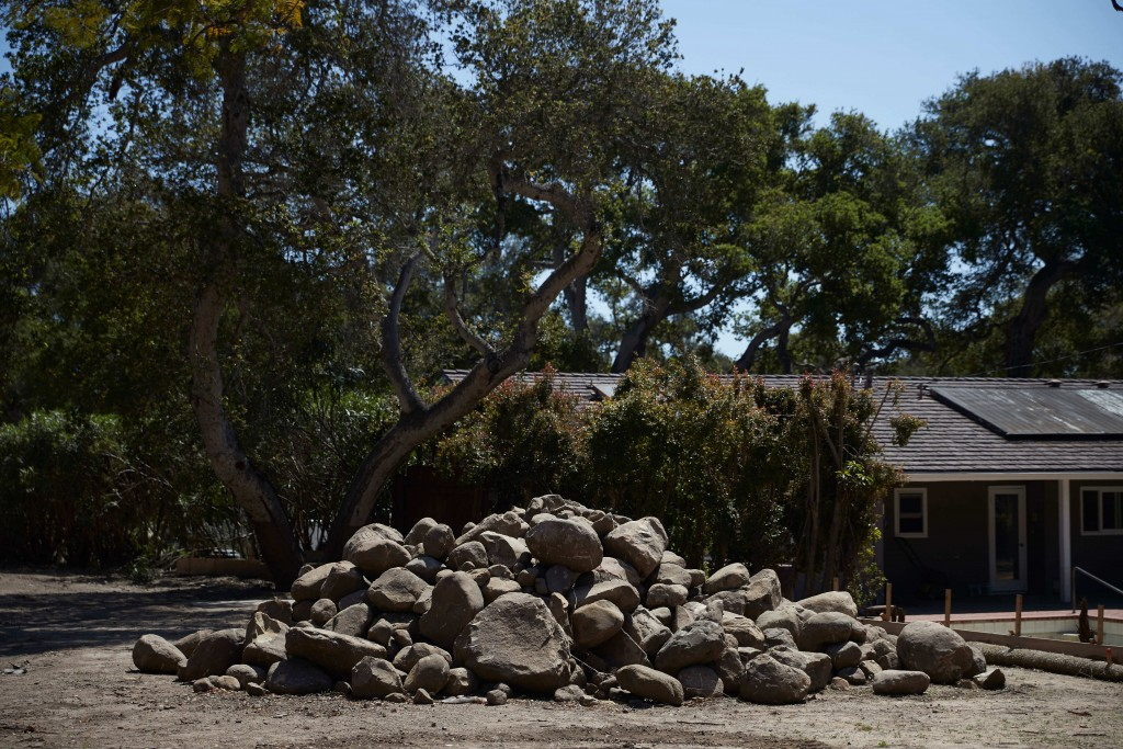 In this Wednesday, April 11, 2018, photo, boulders swept along in a mudslide are piled up in Montecito, Calif. Months after the mudslides nearly wiped