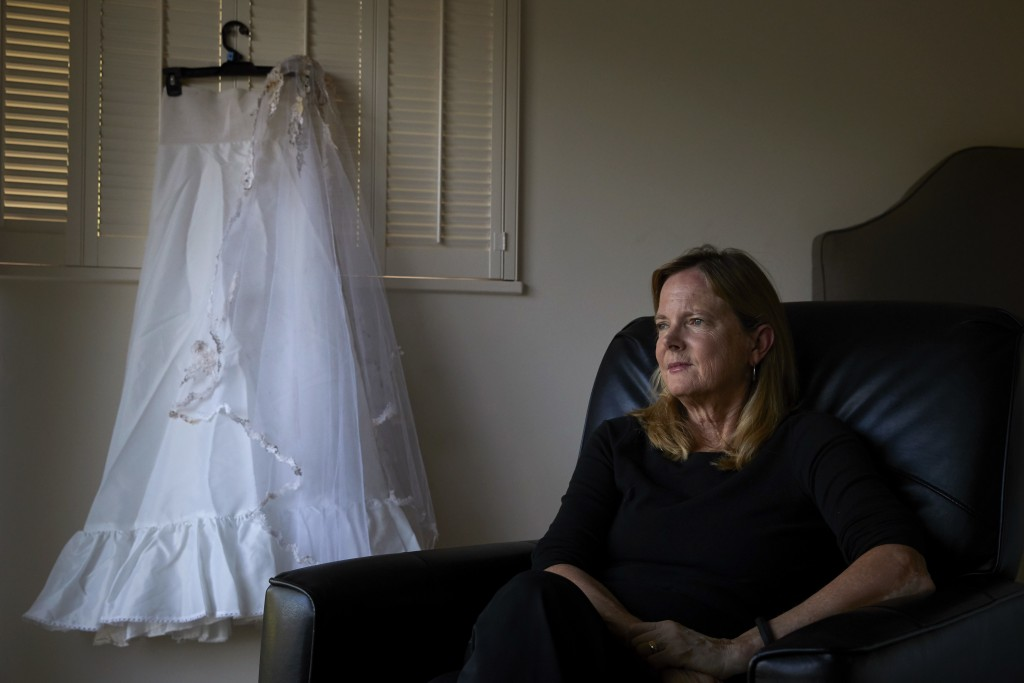In this Wednesday, April 11, 2018, photo, Karen McDonald, whose home was swept away in a mudslide, poses for photos with her wedding veil and the unde