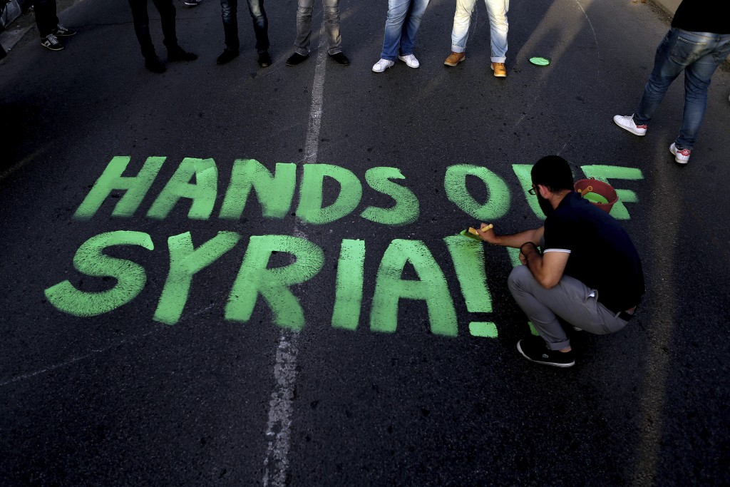 "A protestor paints ""Hands off Syria"" on the street during a protest against the airstrikes on suspected chemical weapons sites in Syria, outside of th"