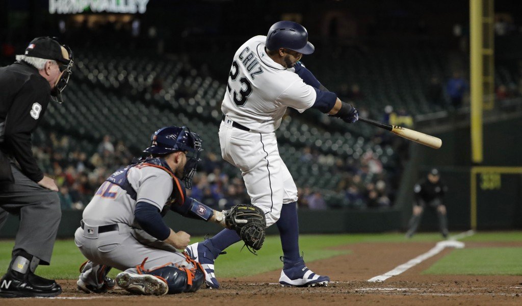 Seattle Mariners' Nelson Cruz hits a solo home run against the Houston Astros in the fourth inning of a baseball game, Monday, April 16, 2018, in Seat