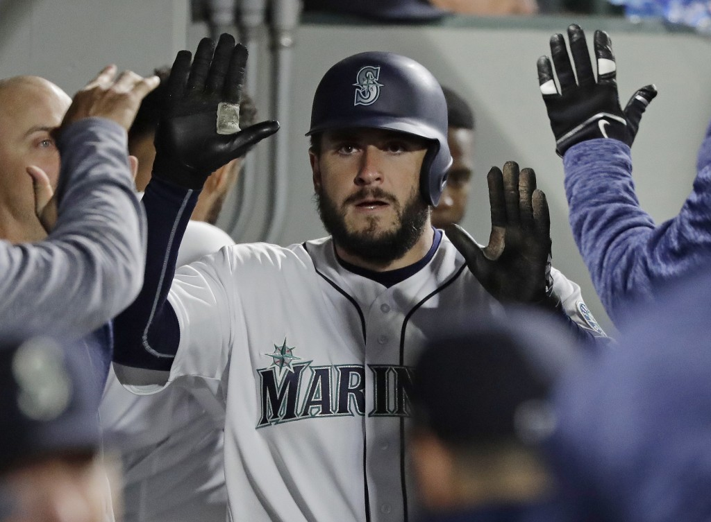 Seattle Mariners' David Freitas is greeted in the dugout after he scored on a double, hit by Dee Gordon during the sixth inning of a baseball game aga