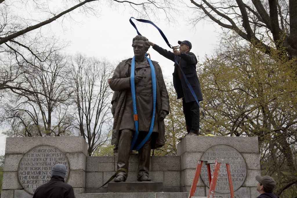 A worker tosses a strap over the 19th century statue of Dr. J. Marion Sims, Tuesday, April 17, 2018, in New York's Central Park.  Sims was known as th
