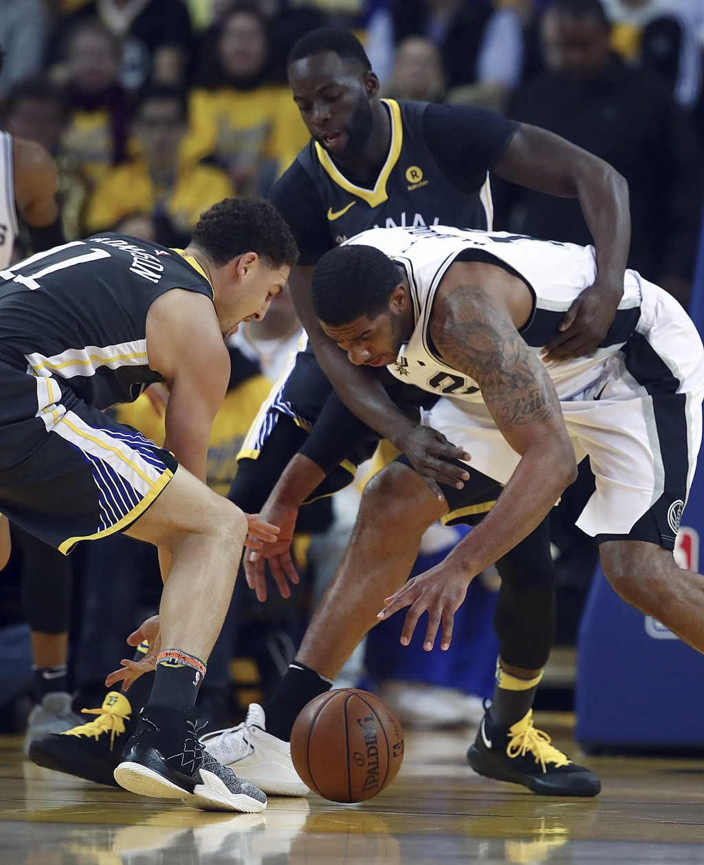 Golden State Warriors' Klay Thompson, left, Draymond Green, center, and San Antonio Spurs' LaMarcus Aldridge (12) fight for a loose ball during the fi