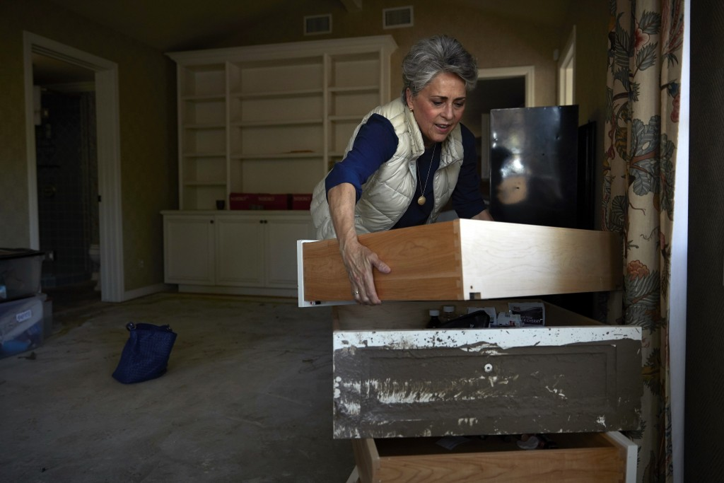 In this Wednesday, April 11, 2018, photo, mudslide survivor Mari Mitchel moves drawers covered in mud in her bedroom, in Montecito, Calif. The mudslid