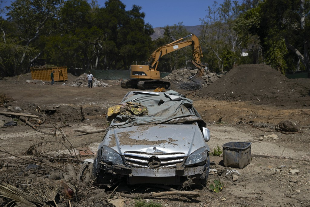 In this Wednesday, April 11, 2018, photo, a mangled car sits in a neighborhood devastated by a mudslide, in Montecito, Calif. Months after the mudslid