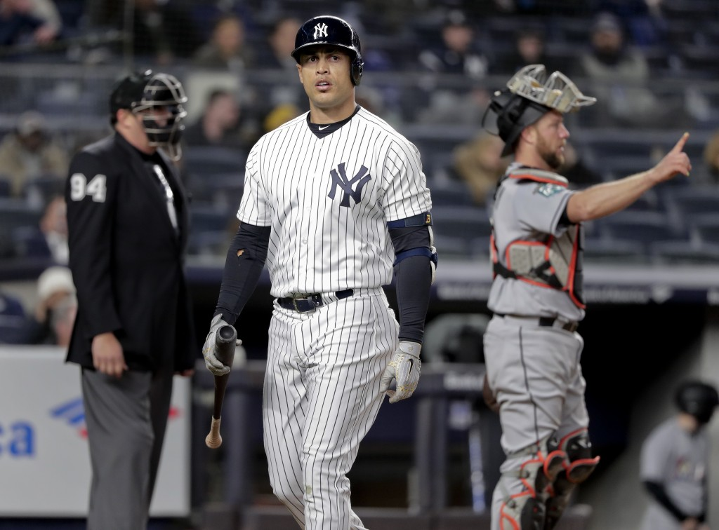 New York Yankees' Giancarlo Stanton walks back to the dugout after striking out against the Miami Marlins during the seventh inning of a baseball game