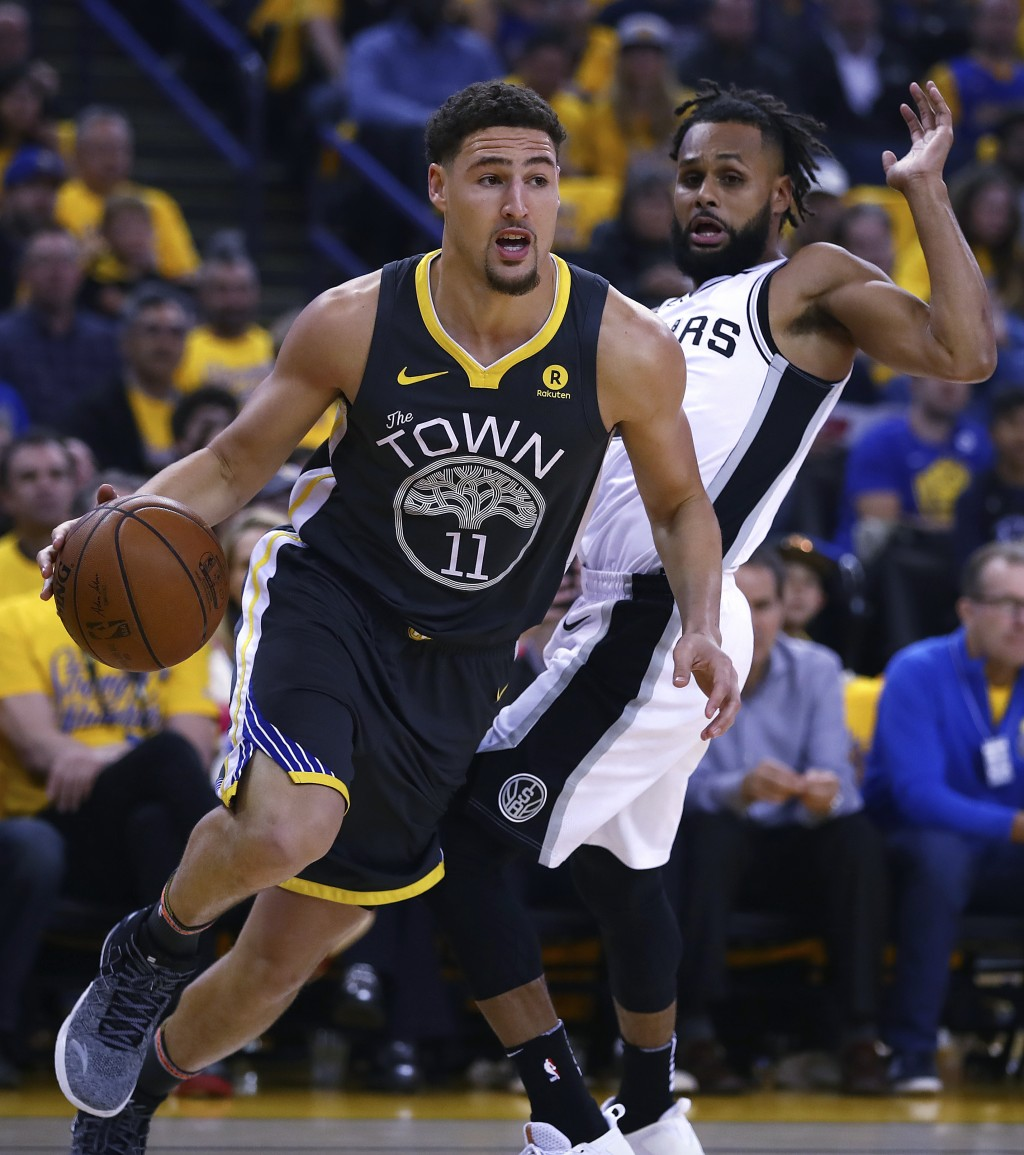 Golden State Warriors' Klay Thompson (11) drives the ball away from San Antonio Spurs' Patty Mills, right, during the first quarter in Game 2 of a fir