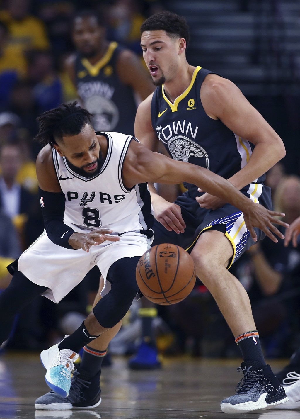Golden State Warriors' Klay Thompson, right, guards San Antonio Spurs' Patty Mills (8) during the first quarter in Game 2 of a first-round NBA basketb