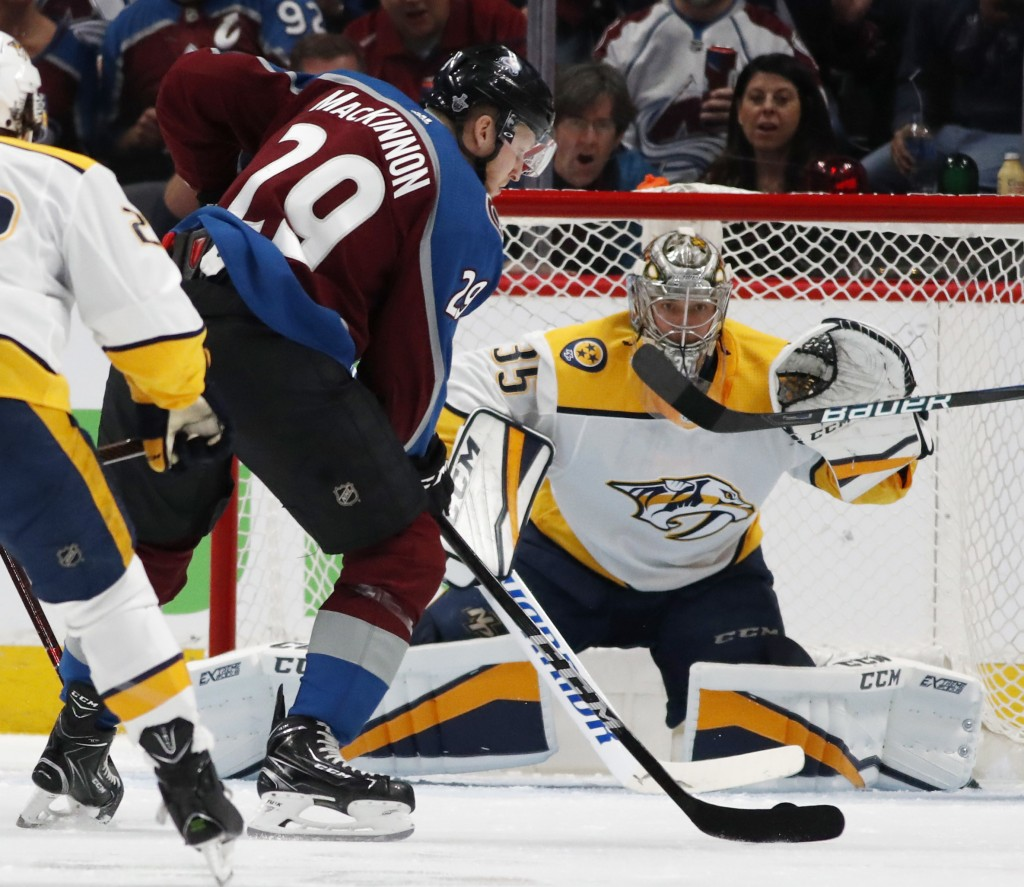 Colorado Avalanche center Nathan MacKinnon, front, fires a shot at Nashville Predators goaltender Pekka Rinne for a goal in the second period of Game