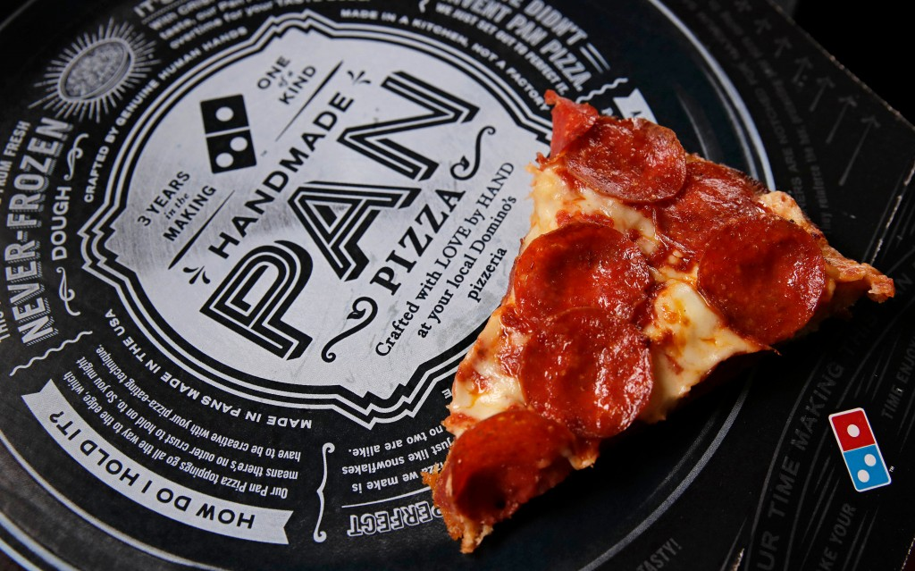 FILE - This Oct. 21, 2016, file photo shows a slice of pepperoni pizza on a Domino's Pizza box in Derry, N.H. Fla. The pizza chain said Monday, April