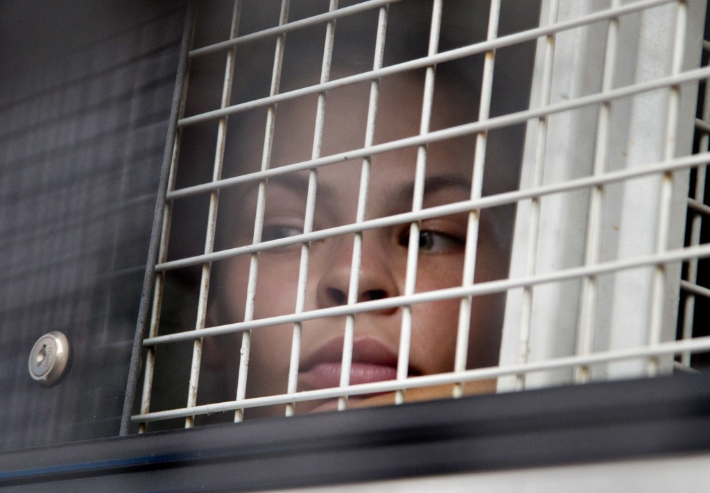 Anastasia Vashukevich sits inside a prison transport vehicle outside a courthouse in Pattaya, south of Bangkok, Thailand, Tuesday, April 17, 2018.  Ru