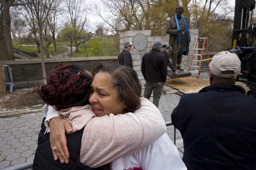 Dr. Bernadith Russell hugs a friend as the statue of Dr. J. Marion Sims, is removed from New York's Central Park, Tuesday, April 17, 2018.  Sims was k