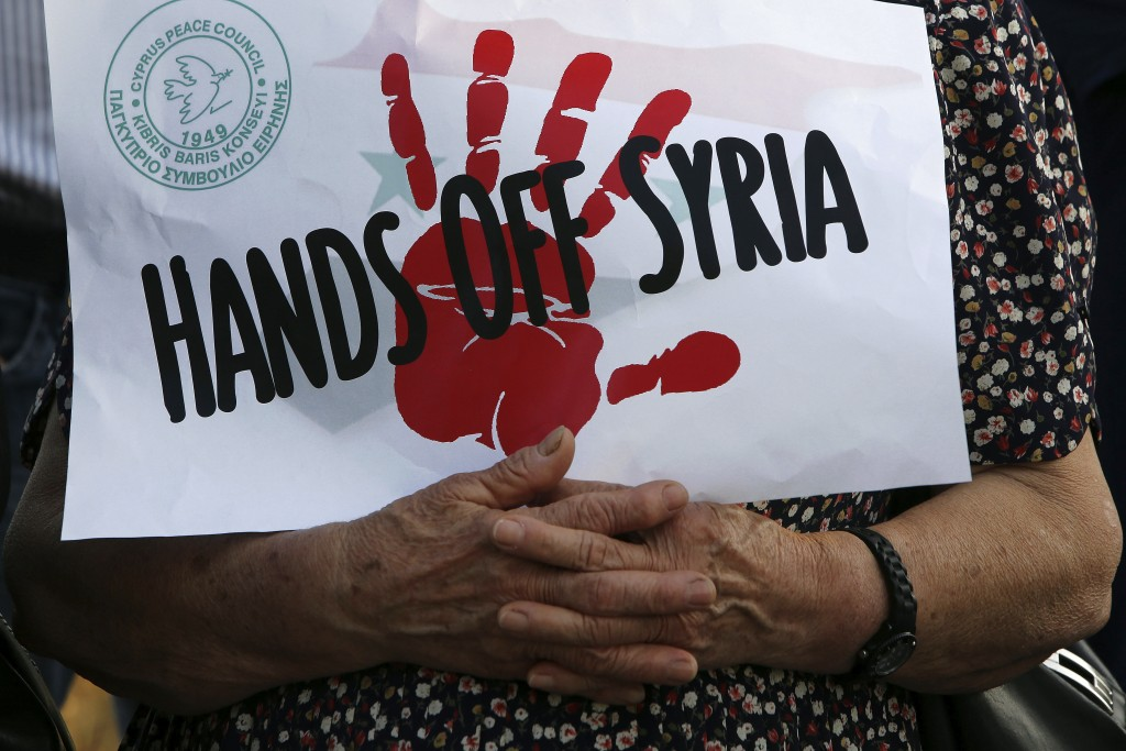 """A protestors holds a banner reading """"Hands off Syria"""" during a protest against the airstrikes on suspected chemical weapons sites in Syria, outside of"""