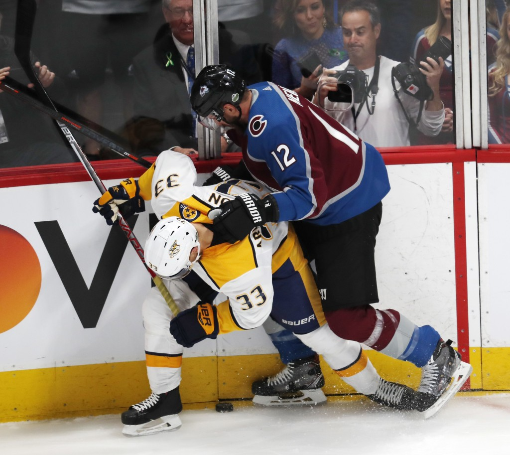 Colorado Avalanche defenseman Patrik Nemeth, hits Nashville Predators left wing Viktor Arvidsson as he tries to control the puck in the first period o