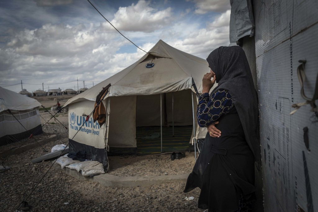 This photo released by Amnesty International on Tuesday, April 18, 2018 shows 33-year-old mother of six, Zahra, outside a tent used for cooking inside
