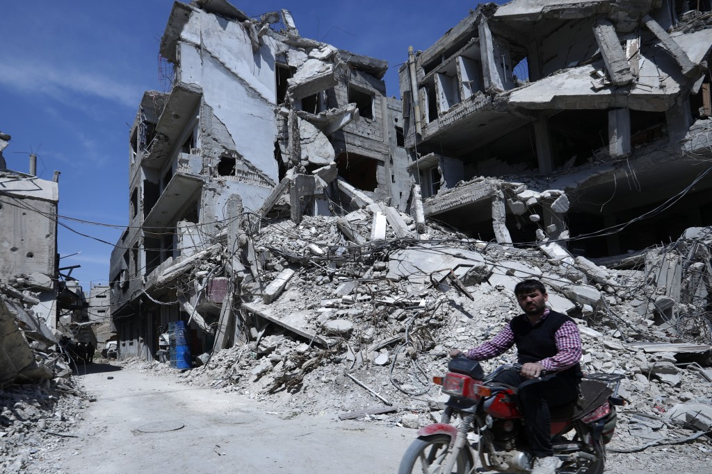 A man rides past destruction in the town of Douma, the site of a suspected chemical weapons attack, near Damascus, Syria, Monday, April 16, 2018. Fais
