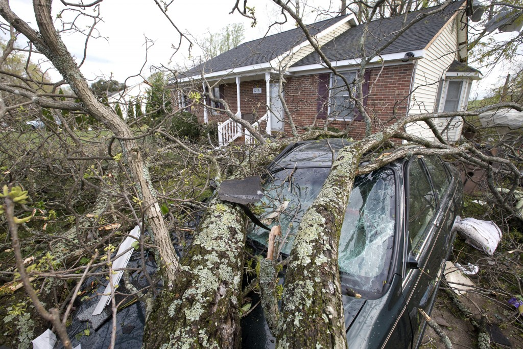 A car on Nealtown Road sits crushed by fallen tree limbs the day after a tornado devastated the eastern portion of the city Monday, April 16, 2018, in