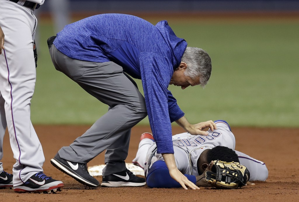 Texas Rangers trainer Kevin Harmon helps shortstop Jurickson Profar after he was injured in a collision with Tampa Bay Rays' Mallex Smith during the s