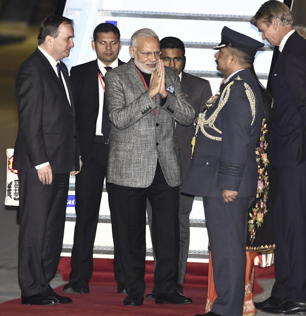 India's Prime Minister Narendra Modi, centre, is greeted by Swedish Prime Minister Stefan Lofven, left, on his arrival at Arlanda Airport in Stockholm