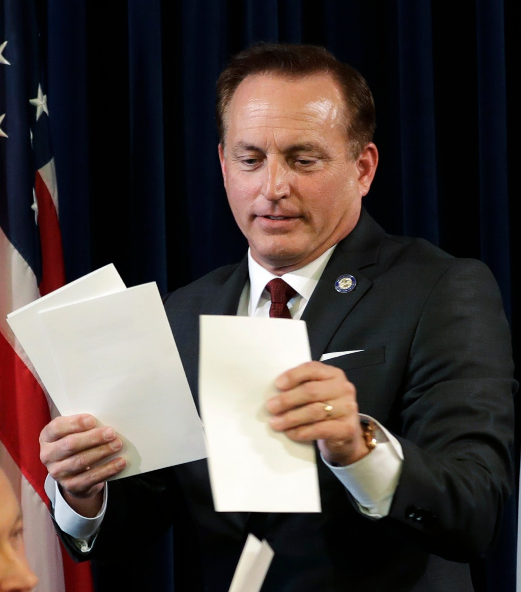FILE - In this Dec. 19, 2016, file photo, Iowa Secretary of State Paul Pate collects ballots during Iowa's Electoral College vote at the Statehouse in
