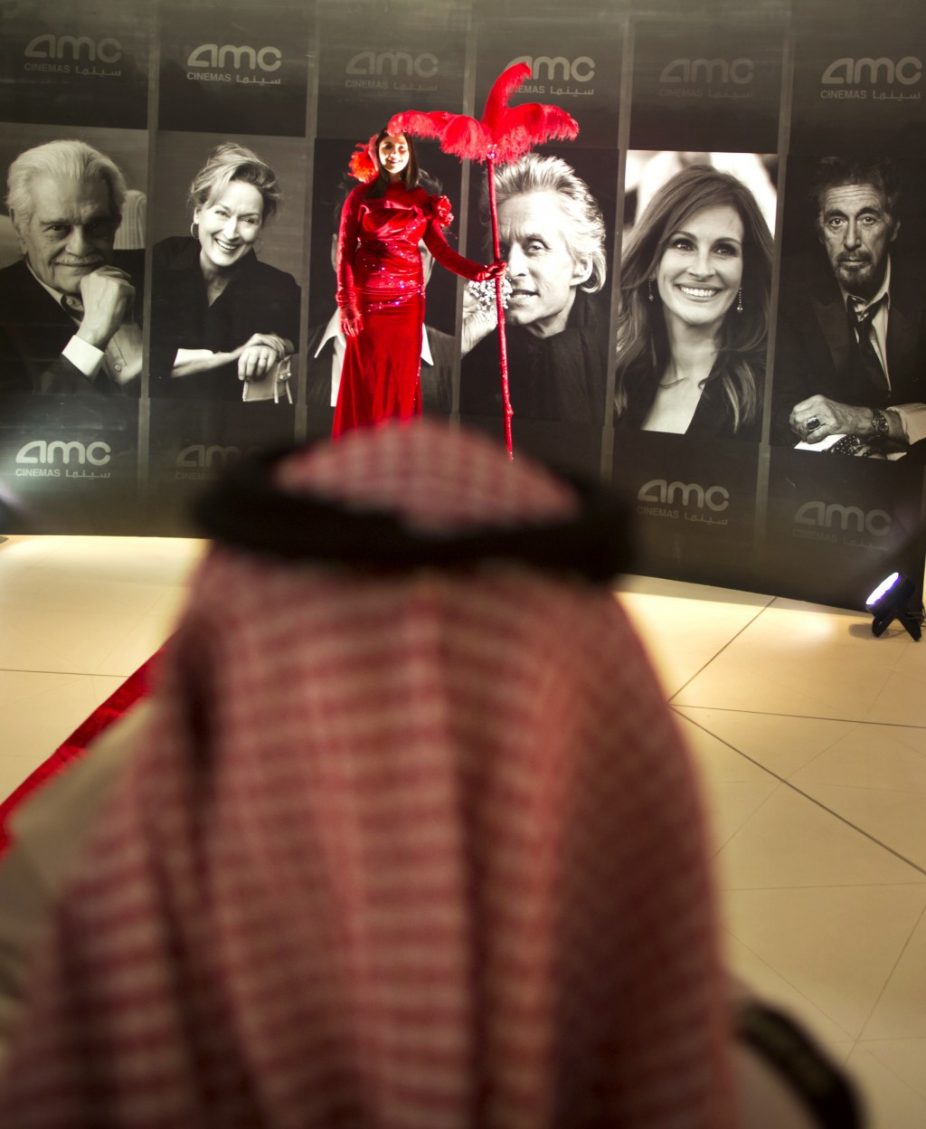 First saudi cinema opens with popcorn and black panther taiwan news a visitor takes pictures for an actress with a red dress in front of posters of hollywood movie stars during invitation only screening at the king ab stopboris Gallery