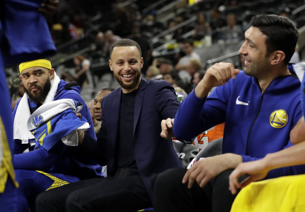 Golden State Warriors' JaVale McGee watches as Stephen Curry, center, jokes with Zaza Pachulia, right, during the second half of Game 3 of the team's ...