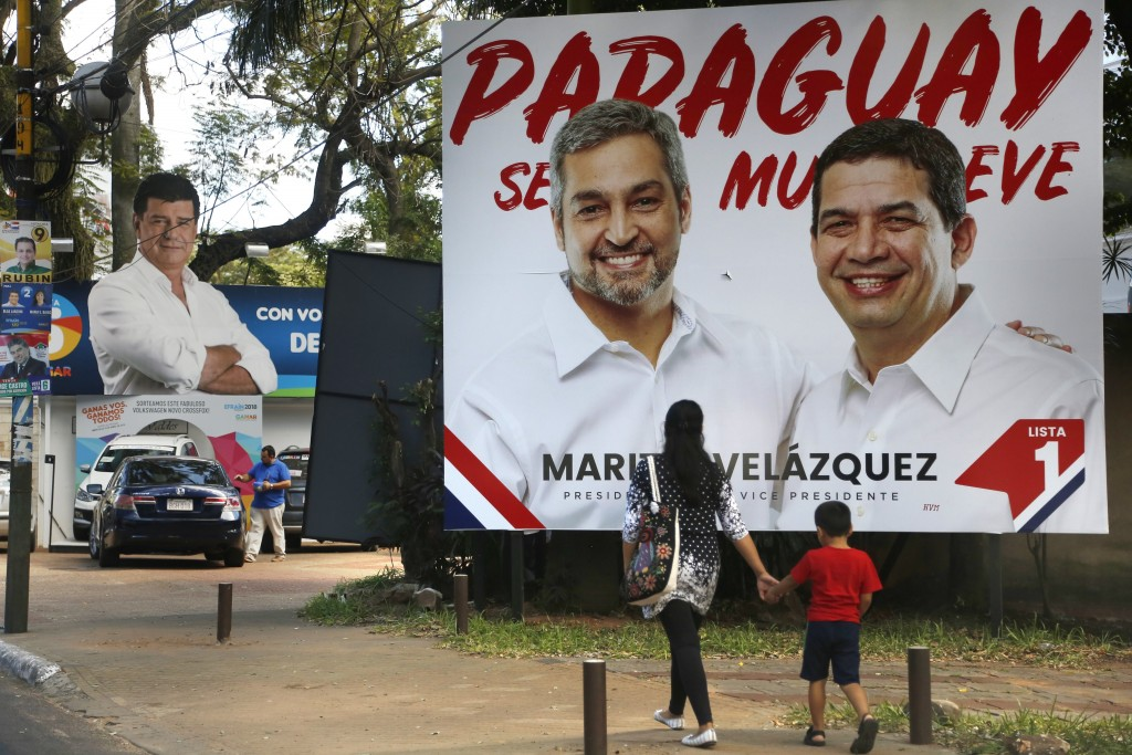 A woman and a child walk past billboards of Colorado Party presidential candidate Mario Abdo Benitez and his running mate Hugo Velazquez, right, and o