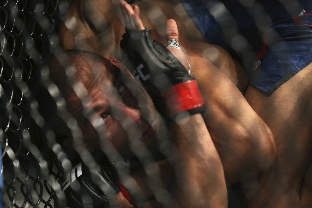 Edson Barboza tries to protect himself as Kevin Lee hits him during the second round of their mixed martial arts lightweight bout, early Sunday, April...