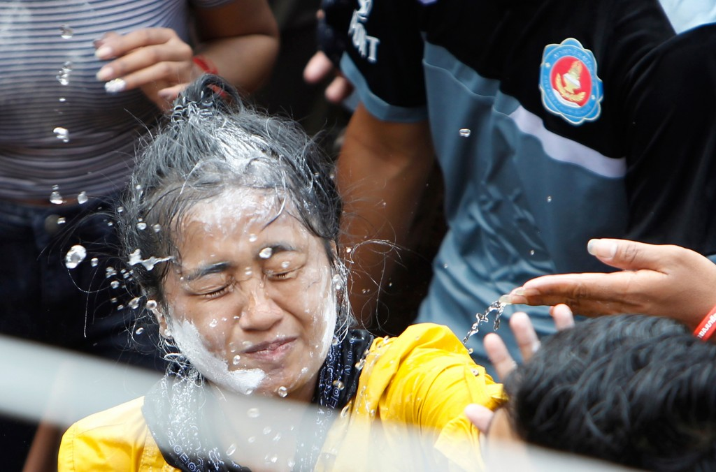 In this Sunday, April 22, 2018, file photo, a girl is painted her face as she gets the holy water poured on her by her friends to mark the end of the ...