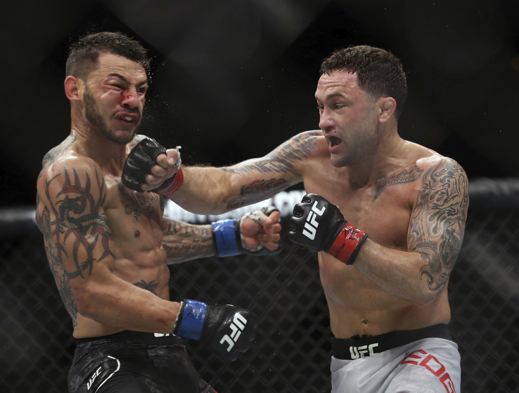Frankie Edgar, right, hits Cub Swanson during the third round of their UFBC mixed martial arts featherweight bout early Sunday, April 22, 2018, in Atl...