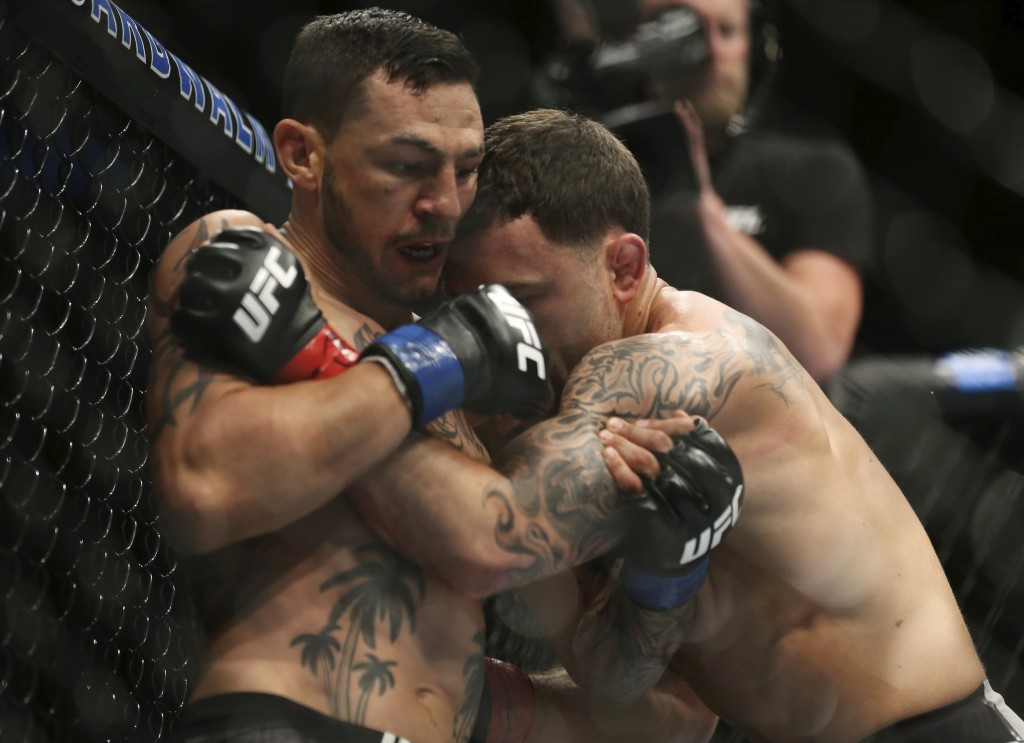 Cub Swanson, left, ties up Frankie Edgar during the third round of their UFC mixed martial arts featherweight bout early Sunday, April 22, 2018, in At...