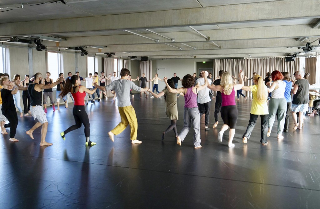 In this Sunday, April 15, 2018 photo a group of people take a part in a workshop, led by Syrian migrants, to learn the traditional Arabic dance Dabke ...
