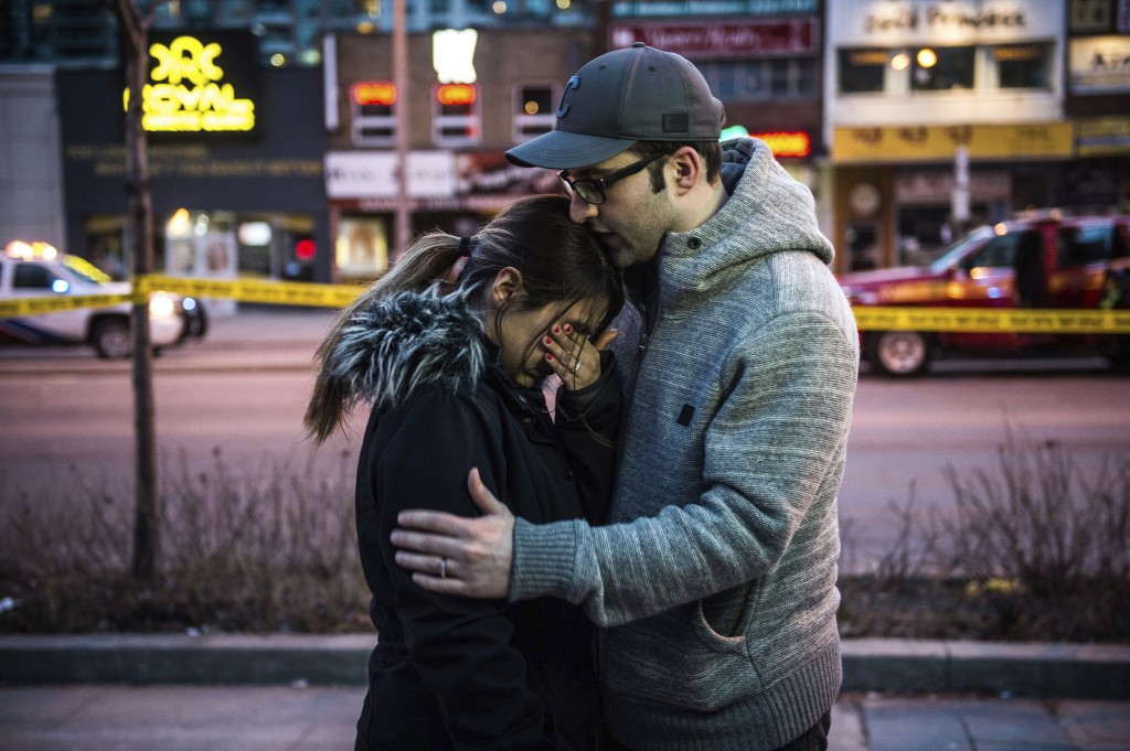 Farzad Salehi consoles his wife, Mehrsa Marjani, who was at a nearby cafe and witnessed the aftermath when a van plowed down a crowded sidewalk, killi...